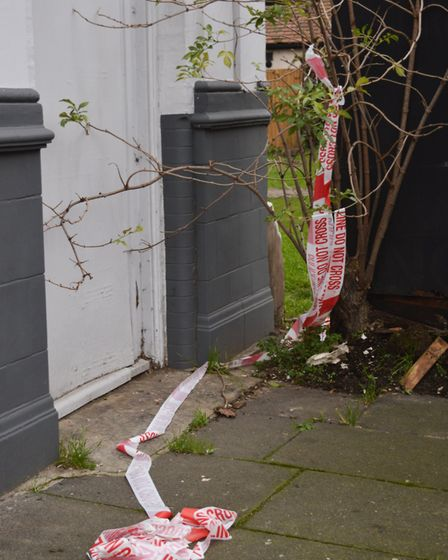 A tattered police cordon lies by the front of the building on Wednesday afternoon. Picture: Hannah S