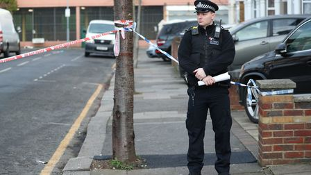A police officer at the scene of a fatal triple stabbing in Elmstead Road. Picture: PA