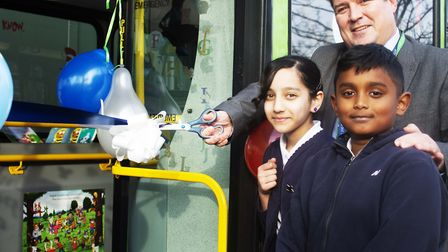 Executive headteacher Darren Williams cuts the ribbon to the reading bus with Central Park Primary S