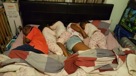 Nosakhare and Joy's children share a bed while their parents sleep on the living room floor. Picture