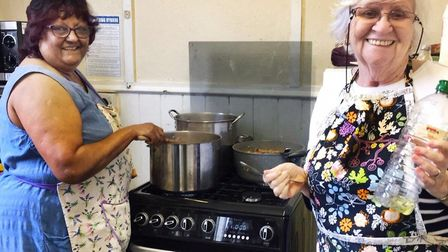 Volunteers Bhati Navsaria and Maureen Kinsey busy cooking takeaway meals. Picture: Bonny Downs Commu