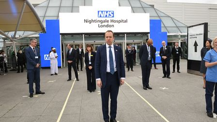 Health secretary Matt Hancock and NHS staff stand on marks on the ground, put in place to ensure soc