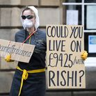 A demonstrator protests about the UK Government sick pay allowance of £94 per week for freelance and