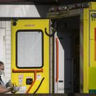 A London Ambulance worker wearing a protective face mask cleans an ambulance after transporting a pa