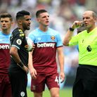 Referee Mike Dean (right) ahead of the VAR check for Manchester City's Sergio Aguero's penalty durin