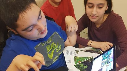 Royal Docks Academy pupil Moeez Nawaz watching a video audiobook with his siblings. Picture: RDA