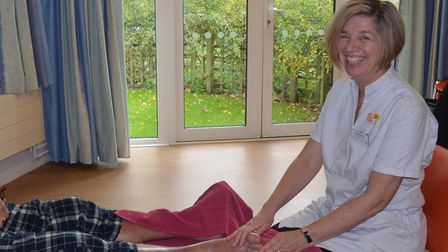 Big smiles as Sharon Williams massages a patient's feet before the corovirus pandemic meant she has