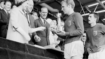 England captain Bobby Moore holds the Jules Rimet Trophy, collected from the Queen, after leading hi
