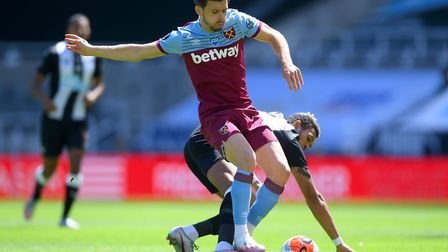 West Ham United's Aaron Cresswell (left) and Newcastle United's Joelinton (behind) battle for the ba