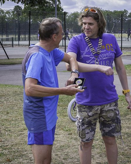 Andy Catton receives his third male handicap medal (Pic: Ilford AC)