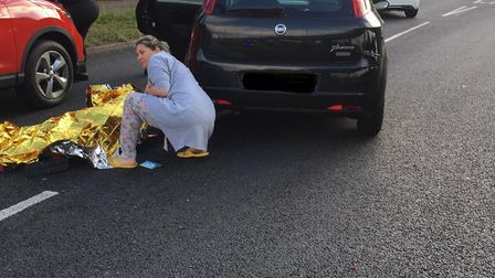A woman tends to a cyclist who was trapped underneath a car in Charlie Browns roundabout. Picture: T