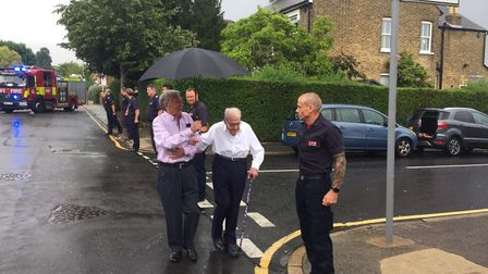 Serving officers form a guard of honour as Ernie Cox is escorted to his 100th birthday celebration,