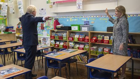Head teacher Bernadette Matthews shows Prime Minister Boris Johnson a sign giving instructions on ho