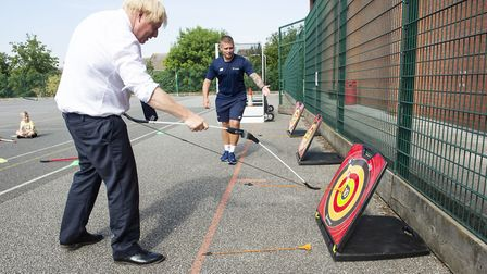 Prime Minister Boris Johnson checks the target board as he takes part in archery during a visit to t