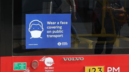 Messages on the side of London buses remind commuters to wear a face covering on public transport. P