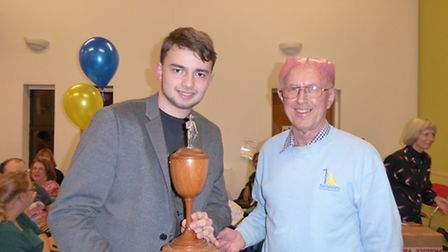 Christian Head receiving a trophy from Richard Morling, Waveney Sailability chairman, at the party