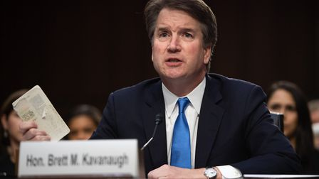 Judge Brett Kavanaugh holds up a copy of the US Constitution as he testifies during the second day o