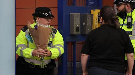 A police officer with flowers outside Croydon Custody Centre in south London where police officer Se