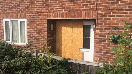 The boarded up door at the four bedroom house. Mindaughes Noreika was caught when answering the door