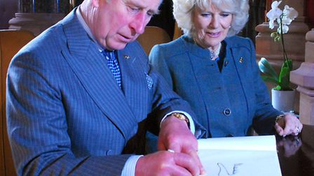 Prince Charles and Camilla sign the visitors' book at The Renaissance Hotel at St Pancras. Picture: