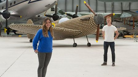 Charlotte and Jack Munro stand next to the life-size Battle of Britain spitfire they created