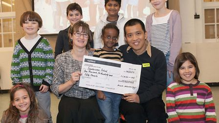 Brookfield Primary School children present a cheque to Vicky Bowman and her husband Htein Lin