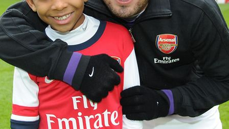 Young Gunner Calvin Da Cruz with Arsenal midfielder Santi Cazorla ahead of Saturday's game against A