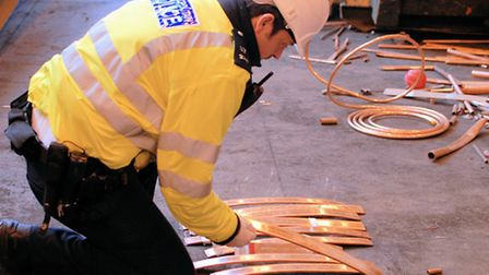 A police officer from the Metals Task Force examines recovered copper elsewhere in London