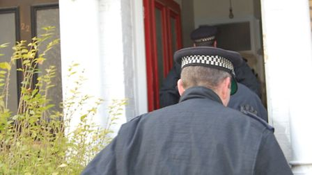 Officers entering a suspected cannabis grower's house during Operation Hawk