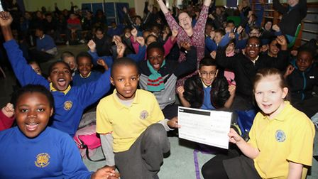 London Fields schoolchildren present a cheque to Helen Cain, from Street Child charity, with the mon