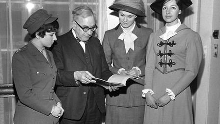 Girls in period costumes gather around historian AJP Taylor for a glance at the first of the 96 week
