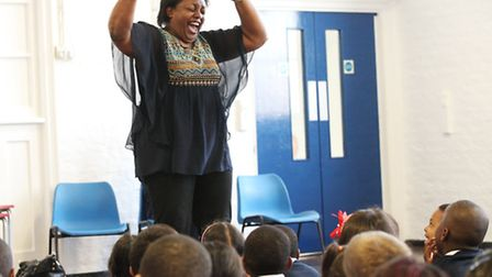 Author Malorie Blackman amuses children with her story-telling at De Beauvoir School's assembly.