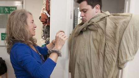 Oxfam Hampstead deputy manager Yvonne Chattington helps Tim Lamden squeeze into his new frock. Pictu