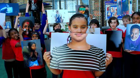 Children from St Silas and Holy Trinity Primary School with the photographs on show at The Strand Ga