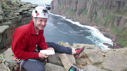Hampstead crime author Red Szell signing a log book on the summit of The Old Man of Hoy for successf