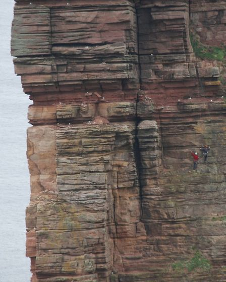 Red Szell and his climbing partners scale the sheer rock face of The Old Man of Hoy