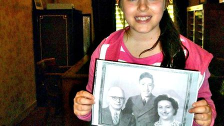 Tali Blitz in Otto Frank's private office holding a picture of her great-grandmother and family