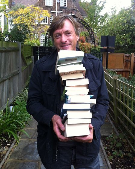 Richard Madeley carries some of his books into Keats Community Library