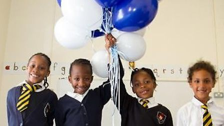 Children hold balloons to celebrate an improved Ofsted at St Matthias Church of England Primary Scho