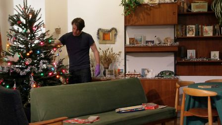 Curator preparing the mid-century room for the Christmas Past exhibition