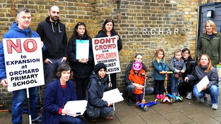 Parents and younger siblings of Orchard School pupils protest outside the chool during a morning of
