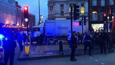 Emergency personnel respond to the collision of a cyclist and a lorry in Camden High Street this aft