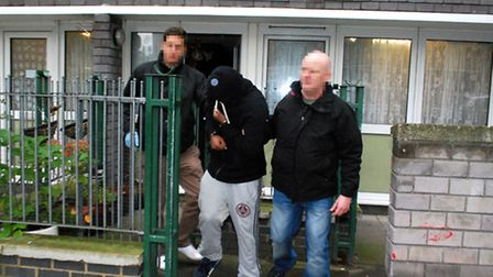 Police bring out a handcuffed suspect during a raid on an address in Euston. Picture: Polly Hancock