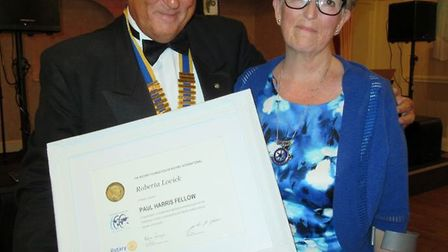 Roberta Lovick is pictured receiving the Paul Harris Fellowship award from the outgoing President of