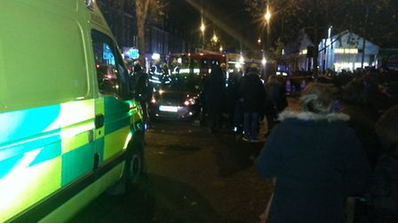 People look on as emergency services attend to a woman injured in a car collision in Stamford Hill l