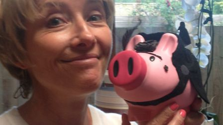 Emma Thompson posing with a Pigs4Kids piggy bank.