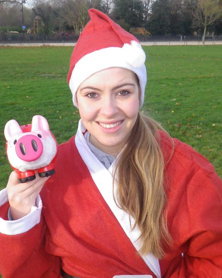 Ellie Petch in her Santa costume showing off a Pigs4Kids piggy bank before the race.