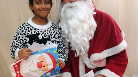 Nadia Hallpike, 8, is pictured meeting Santa Claus in his grotto at the St Michael and All Angels C