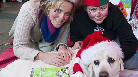 Kelly Craig and Anna Chilton, dressed as elves, with Merlin as Father Christmas at the Santa Paws fa