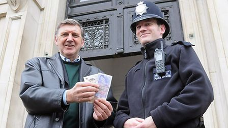 Ham&High editor Geoff Martin offers £30 to Sgt Ryan Keating outside the Old Hampstead Town Hall